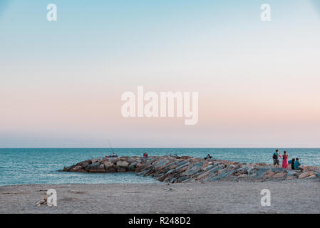 Horizontal photo with stone breakwater. Breakwater goes to blue sea. Sand beach is in front of sea. Clear evening sky is with few clouds. Several pers - Stock Photo