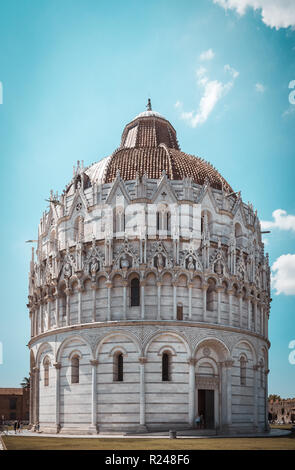 Vertical photo with famous babtistry Battistero di San Giovanni in Pisa. Building is on square Piazza dei Miracoli with leaning tower. Sky is light bl - Stock Photo
