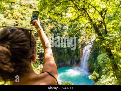 A tourist taking a picture of the Rio Celeste waterfall in Tenorio Volcano National Park, Costa Rica, Central America - Stock Photo
