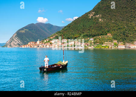 Fisherman with a view of Peschiera Maraglio, Monte Isola, the largest lake island in Europe, Province of Brescia, Italy, Europe - Stock Photo