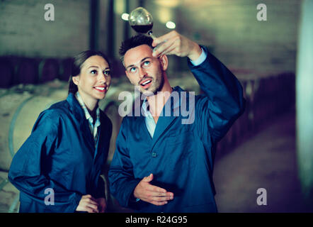 Portrait of young smiling diligent man and woman wearing coats holding glass of wine in winery cellar - Stock Photo