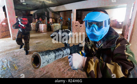 Portrait of blue team happy cheerful player who is aiming in opponents on paintball field. - Stock Photo