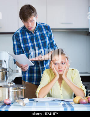 Family couple sitting at desk with documents and counting budget - Stock Photo