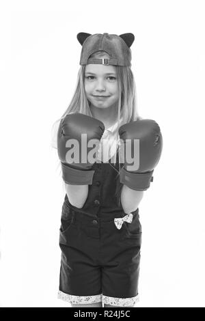 Lovely child wearing huge red boxing gloves. Girl in pink overalls isolated on white background. Kid wearing cute cap with animal ears backwards. Little fighter on training, self defence concept. - Stock Photo
