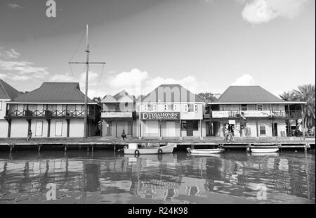 St johns, Antigua - March 05, 2016: boats docked in sea at village quay with houses on blue sky. Summer vacation on tropical island. Discovery and adventure. Wanderlust. - Stock Photo