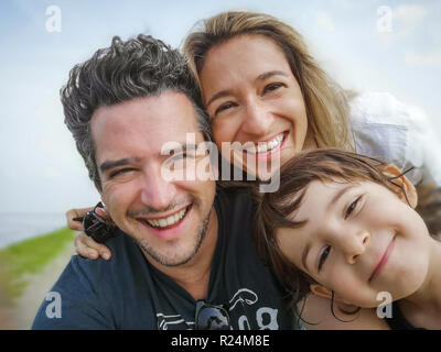 caucasian family portrait selfie only son thirty year old parents only son child . - Stock Photo