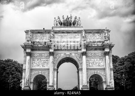 Arc de triomphe du carrousel in paris, france. Arch monument and green trees on cloudy sky. Architectural symbol of peace victory and fame. Vacation and wanderlust in french capital. - Stock Photo