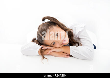 Schoolgirl cute ponytail hairstyle. Excellent pupil lean on desk isolated white. Perfect schoolgirl with tidy fancy hair. School hairstyle ultimate top list. Prepare your kid for first school day. - Stock Photo