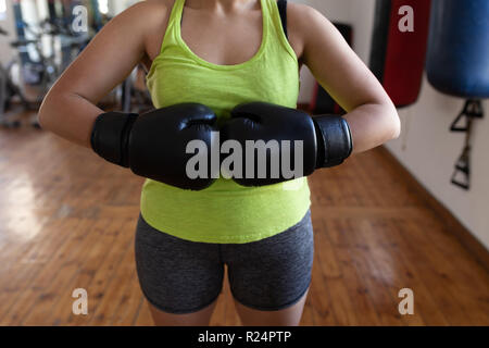 Female boxer standing with boxing gloves in fitness studio - Stock Photo