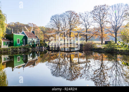 Historic Dutch scene with a bridge, wooden barn and water windmill in the open air museum in Arnhem in the Netherlands - Stock Photo