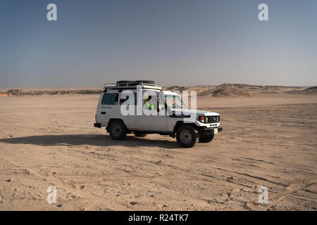 hurghada, Egypt-February 26, 2017: Desert race. Car suv overcomes sand dunes obstacles. Competition racing challenge desert. Offroad vehicle racing obstacles. Car drives offroad with clouds of dust. - Stock Photo