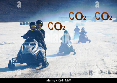 Tourists riding through a stinking fog of exhaust fumes from skidoos on the Langjokull ice sheet in Iceland. Like all of Iceland's glaciers it is retr - Stock Photo