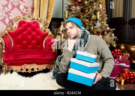 Winter holidays preparation, celebration. Man with thinking face in hat, sweater hold wrapped presents. Guy with gift boxes sit at Christmas tree. New year, xmas, eve, party. Boxing day concept. - Stock Photo