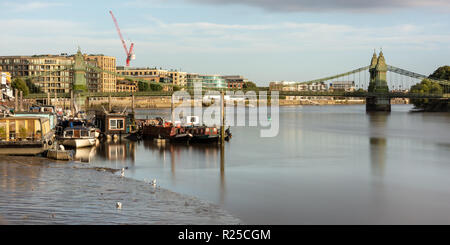 London, England, UK - September 9, 2018: Houseboats are moored at a jetty on the River Thames beside the Hammersmith Suspension Bridge in West London. - Stock Photo