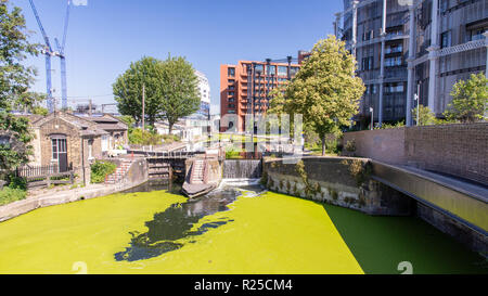 London, England, UK - June 26, 2018: Cyclists and pedestrians pass St Pancras Lock on the Regent's Canal towpath at Gasholders Park in the King's Cros - Stock Photo