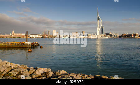 The skyline of Portsmouth, including the Spinnaker observation tower, is lit on a sunny winter day, as seen from across Portsmouth Harbour in Gosport. - Stock Photo