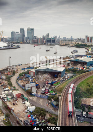 London, England, UK - September 14, 2013: A Docklands Light Railway (DLR) train passes recycling warehouses on an industrial estate beside the River T - Stock Photo
