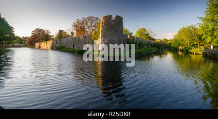 Wells, England, UK - May 25, 2013: The mediaeval castle walls of the Bishop's Palace rise from a moat in the small city of Wells in Somerset. - Stock Photo