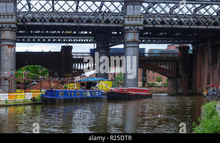 Manchester, England, UK - June 5, 2012: A container freight train crosses Castlefield Basin, where traditional narrowboats are moored on the Bridgewat - Stock Photo