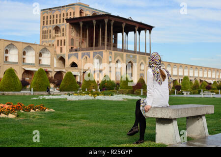 Iran, Ali Qapu Palace  is a grand palace in Isfahan on Naqsh-e Jahan Square in Isfahan (Esfahan). Tourist looking on the palace - Stock Photo