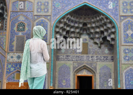 Tourist in front of the main gate to Sheikh Lotfollah Mosque is one of the architectural masterpieces of Iranian, standing on the eastern side of Nagh - Stock Photo