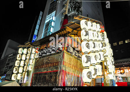 KYOTO, JAPAN - JULY 15, 2011: A portable shrine covered in red and gold embroidered cloth and attached to glowing paper lanterns - Stock Photo