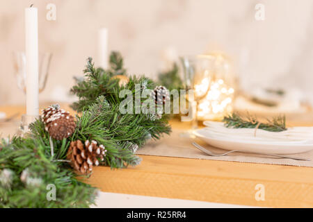 Christmas table setting. Beautiful served table with decorations, candles and lanterns. Living room decorated with lights and Christmas tree. - Stock Photo