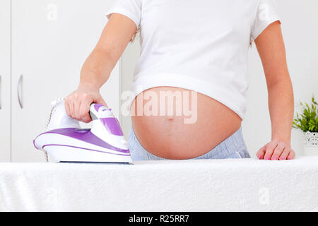 Closeup shot of pregnant woman ironing - Stock Photo