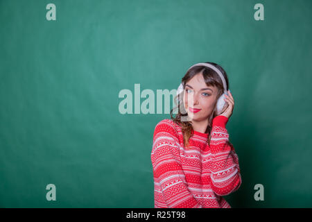 Winter Beauty Woman on green wall background. Winter holidays concept. Skin and hair care in cold season. Beautiful woman with long hair wearing sweater and earmuffs.Copy space - Stock Photo