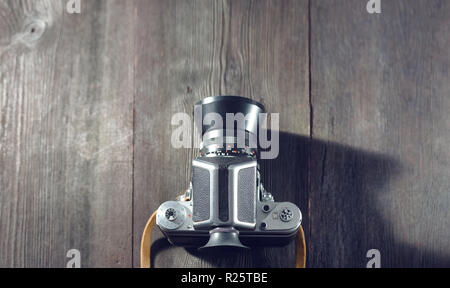 German Vintage photo camera 'Pentacon Six' on a wooden table copyspace - Stock Photo