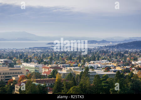 View towards Berkeley and Richmond on a sunny but hazy autumn day; University of California campus buildings in the foreground, San Francisco bay area - Stock Photo