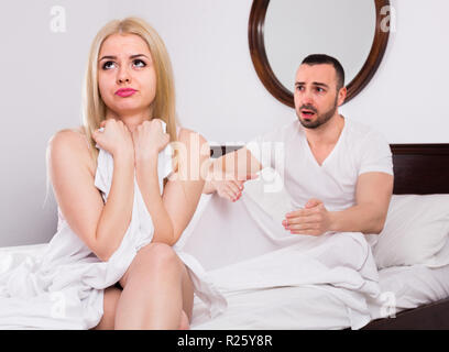Upset young husband pleading in front of offended wife - Stock Photo