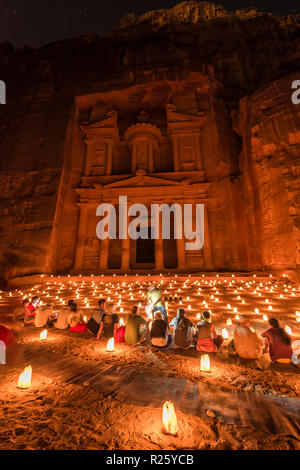 People sitting in front of candles, Pharaoh's treasure house beaten into rock at night, facade of the treasure house Al-Khazneh, - Stock Photo