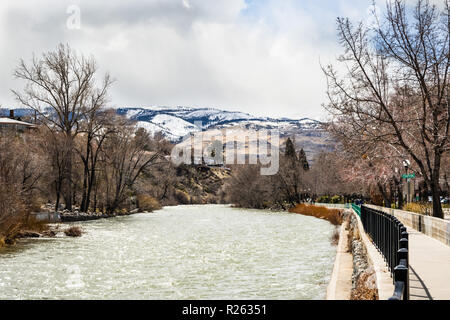 Truckee River flowing through downtown Reno on a cloudy spring day, Nevada; Paved walking path on the right; Sierra mountains covered in snow  in the  - Stock Photo
