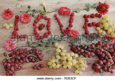 this is raspberry and word love from berries, decorated with flowers, fruits and berries on the wooden background - Stock Photo