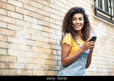 Happy Arab girl using smart phone on brick wall. Smiling woman with curly hairstyle in casual clothes in urban background.