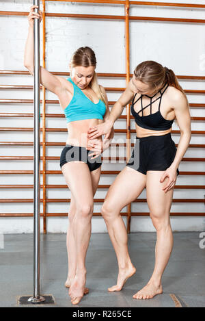 Two glad positive smiling slim girls discussing their bodies during training in fitness gym - Stock Photo