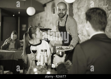 Polite waiter bringing ordered dishes to young smiling couple at restaurant - Stock Photo