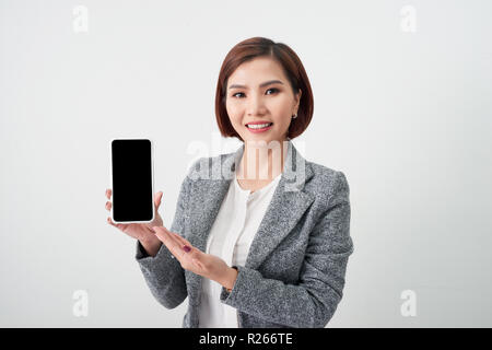 Attractive young Asian woman showing mobile smart phone in her hands. Internet of things concept. - Stock Photo