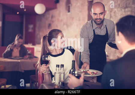 Polite young waiter bringing ordered dishes to smiling couple at restaurant - Stock Photo