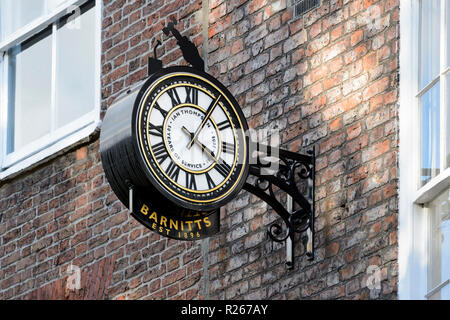 Close-up of public clock telling the time, mounted high on brick wall outside Barnitt's home and garden shop - York, North Yorkshire, England, UK. - Stock Photo