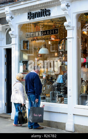 Mature couple standing outside Barnitt's home & garden shop, window shopping & viewing lamps in lighting display - York, North Yorkshire, England, UK. - Stock Photo