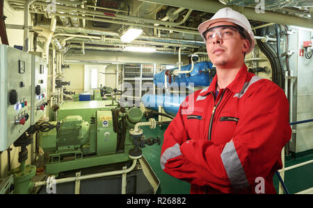 Ship's mechanic near marine diesel generators on a merchant ship in the engine room with all the piping, generators, turbins, etc. writing something d - Stock Photo