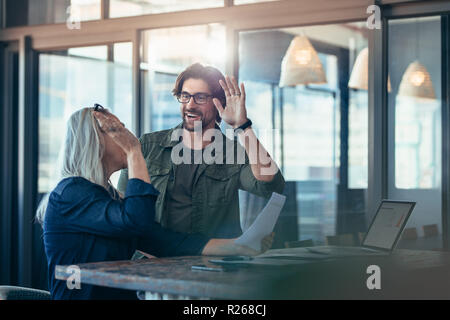 Two business colleagues giving each other a high five and smiling. Business team rejoicing success. - Stock Photo