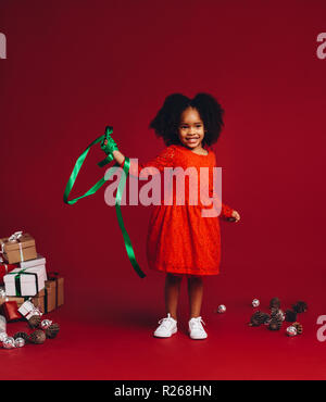 Kid playing with a decorative satin ribbon standing beside gift boxes. Little girl standing against a red background playing with a ribbon. - Stock Photo