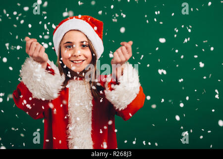 Portrait of a smiling girl enjoying artificial snowfall. Cheerful girl dressed as santa claus standing against green background with artificial snow f - Stock Photo