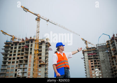 Architect showing buildings on a construction site during a housing project - Stock Photo
