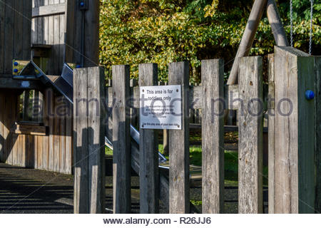 View looking into the deserted toddlers play area with a sign on the open gate reading Toddlers Only in Shapwick, Dorset, England, UK - Stock Photo