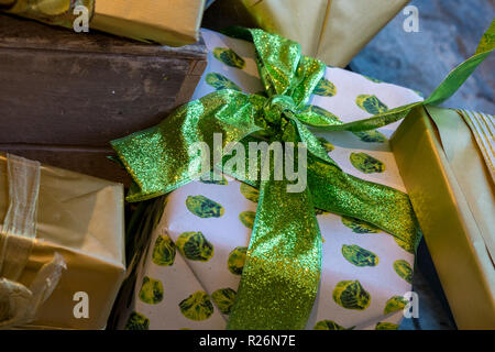 brussels sprouts wrapping paper for christmas presents tied with bright green ribbon under the christmas tree. - Stock Photo