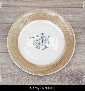 some nuts and bolts in a plate on a wooden table - Stock Photo